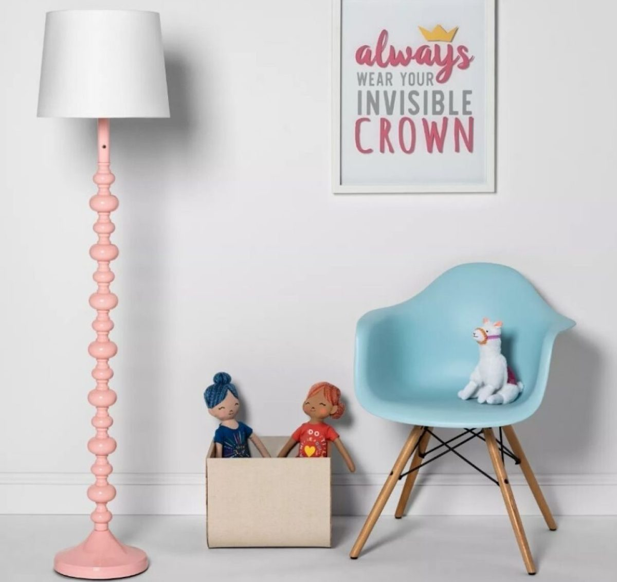 childrens room with lamp, box of toys, chair with stuffed animals, and picture on the wall