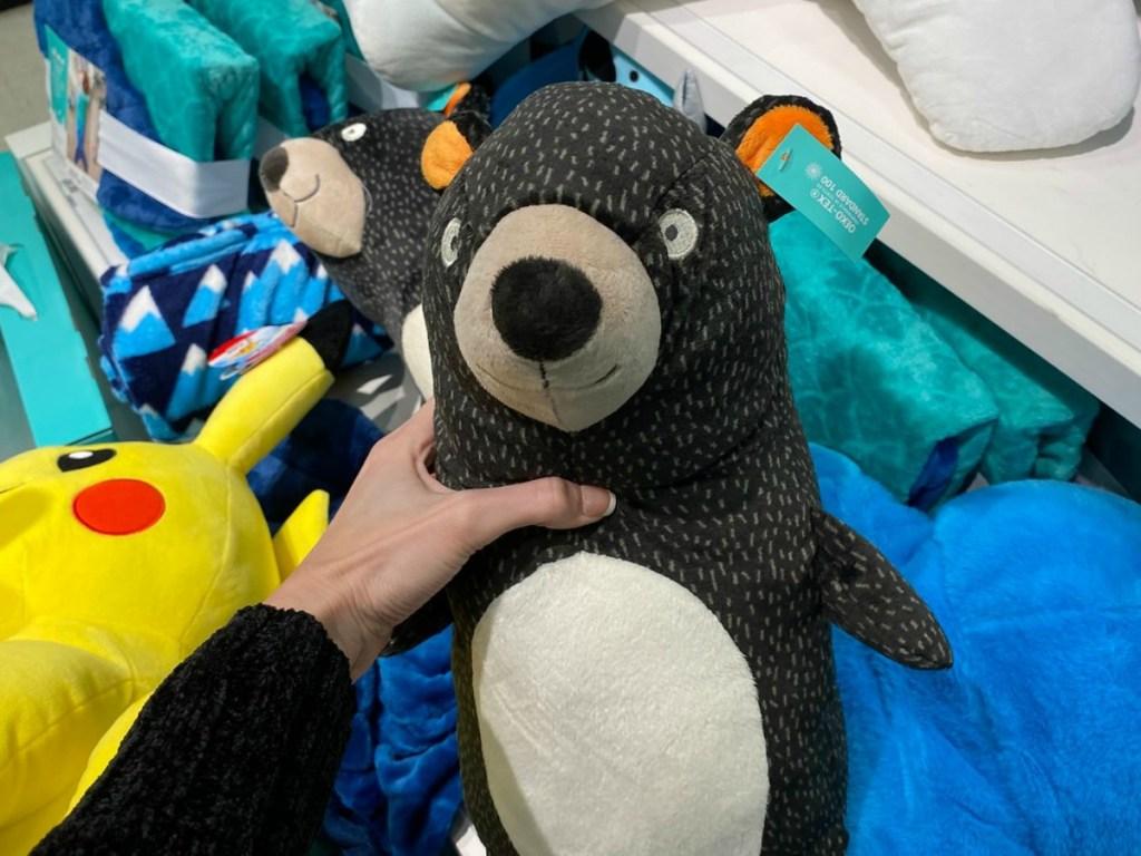 hand holding stuffed bear by store shelves