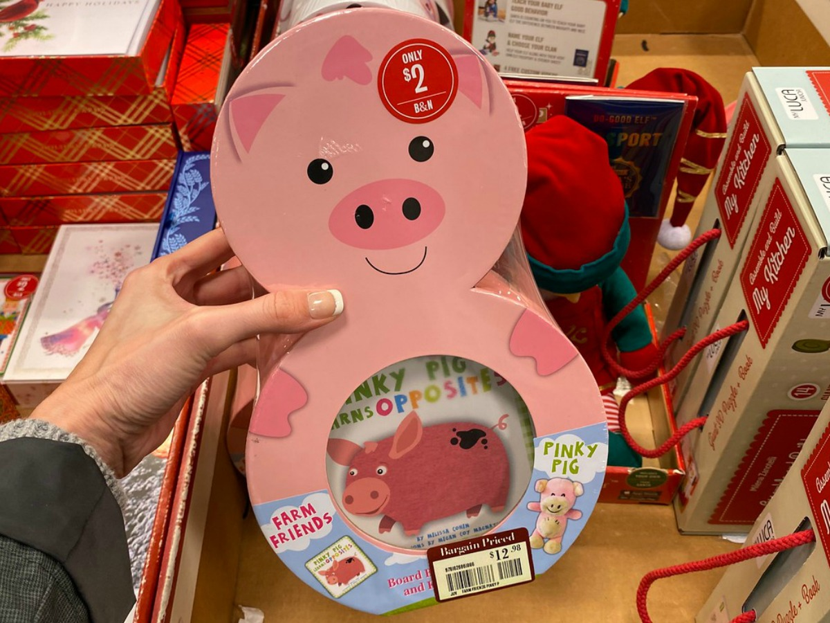 hand holding board book shaped like a pink pig