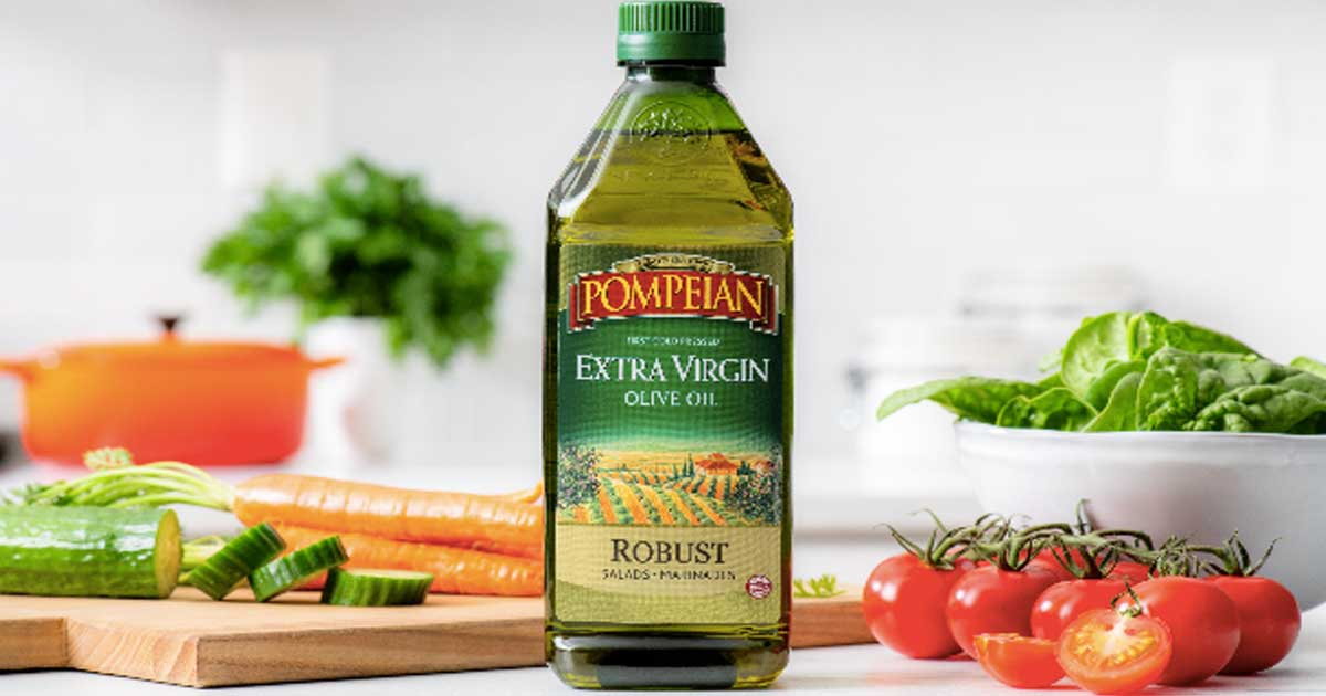 large bottle of extra virgin olive oil on table with food