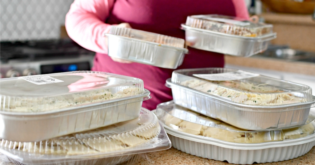 woman holding prepared meals in foil containers