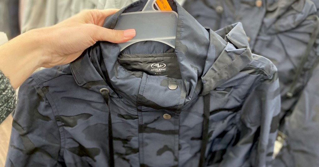 hand holding blue and black camo ran jacket on clear hanger