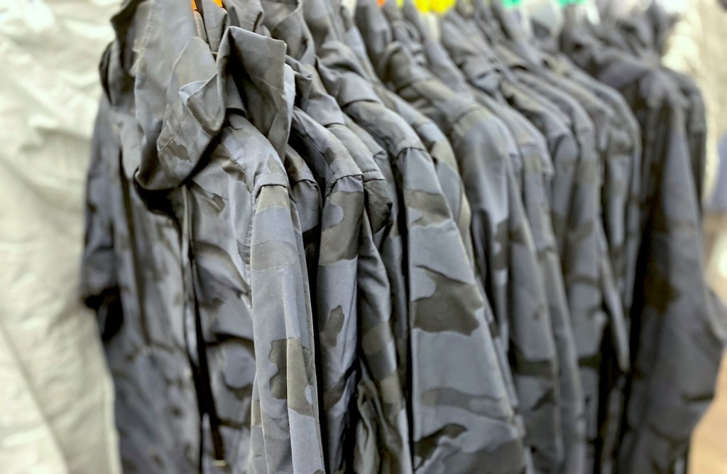 row of black and blue camo jackets hanging in store