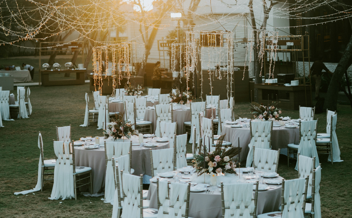 outdoor wedding with tables chairs and various string lights hanging from sky - dollar tree wedding