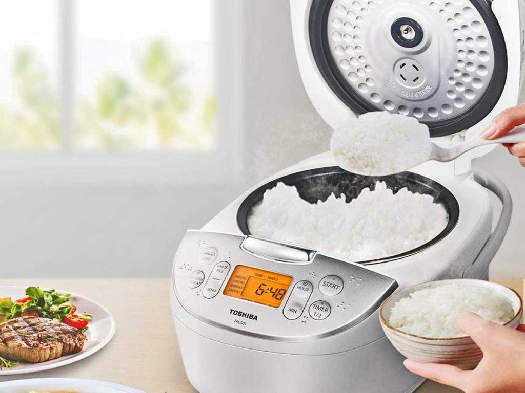 person scooping out rice from rice cooker