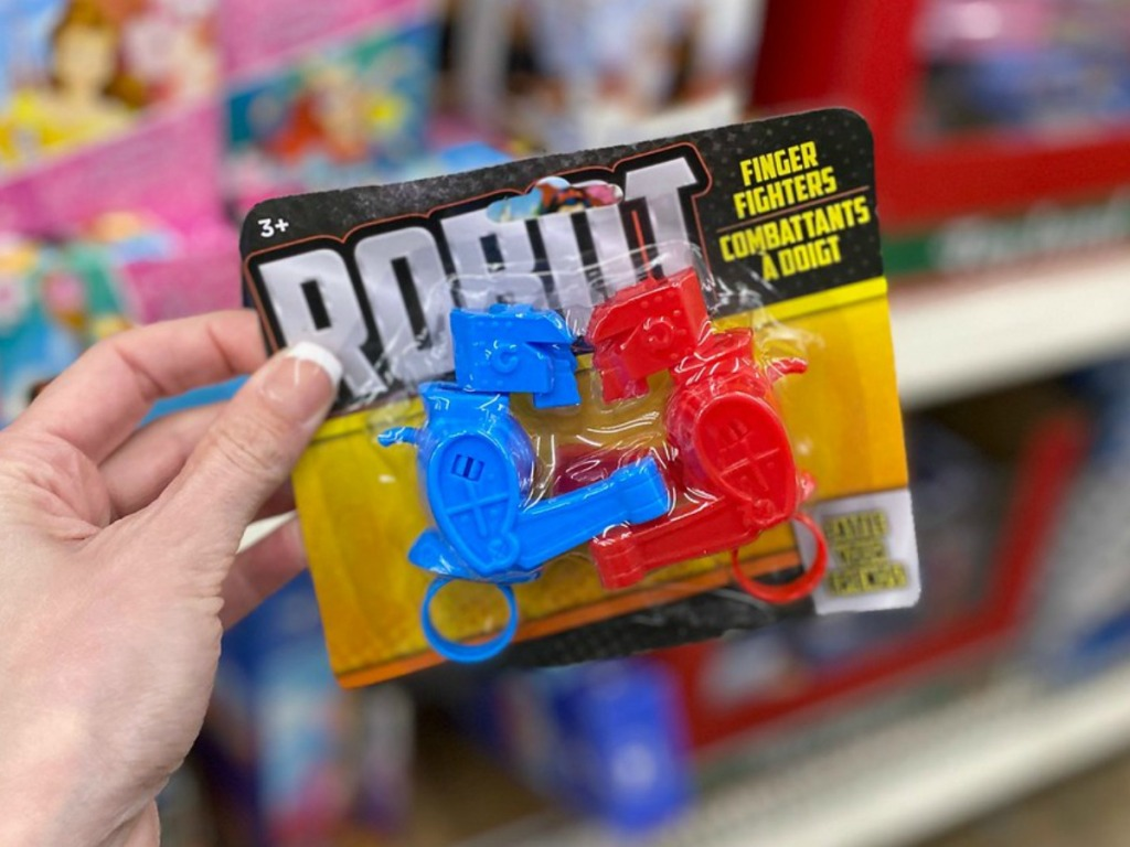 hand holding little package of toy robots by store display