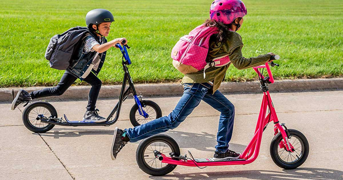kids riding scooters on a sidewalk