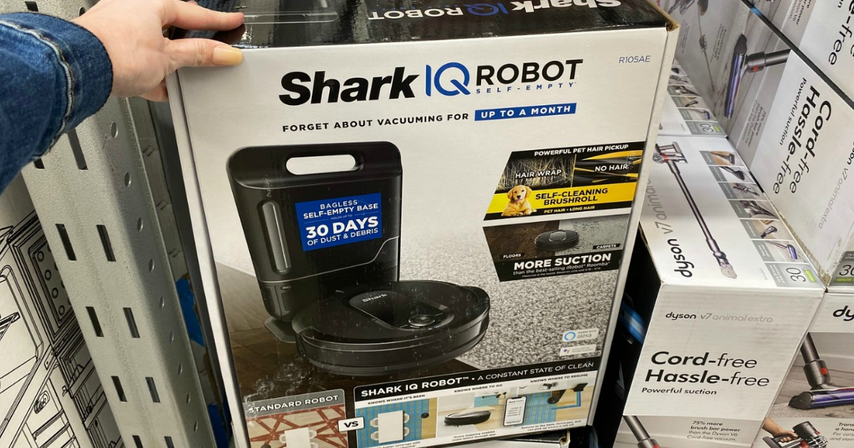hand touching box with shark IQ robot vacuum at Sam's Club