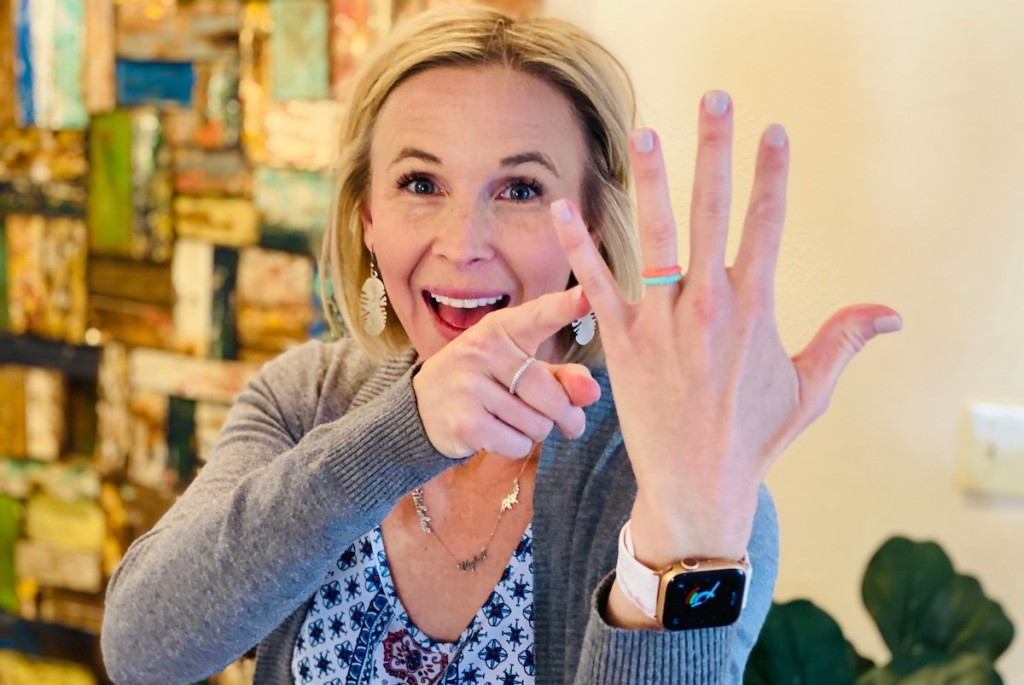 Woman smiling pointing to her ring finger with silicone alternative engagement rings