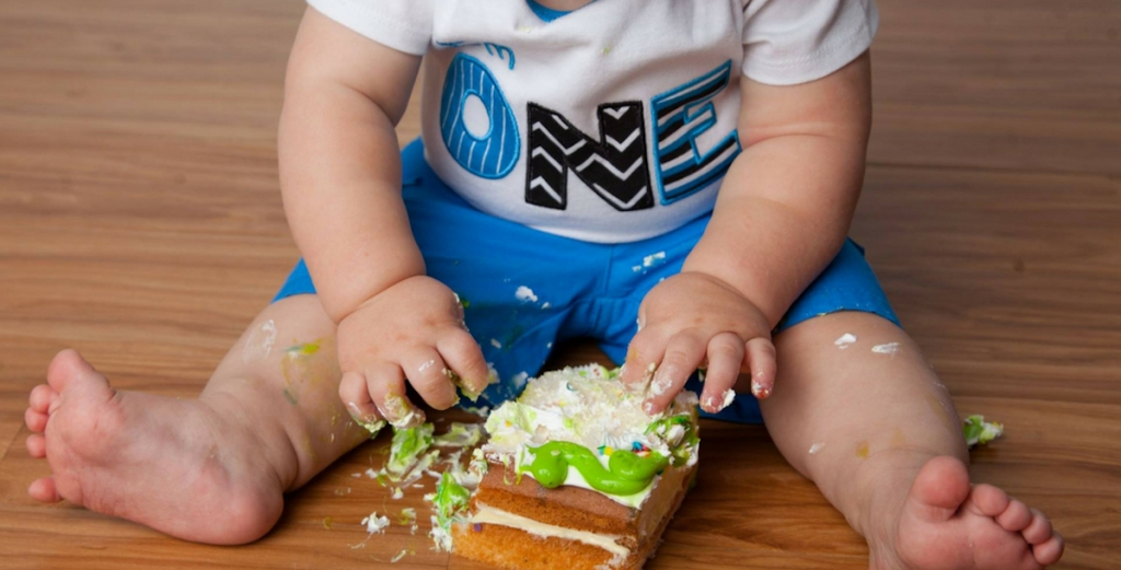 baby with one shirt sitting on wood floor touching piece of birthday cake