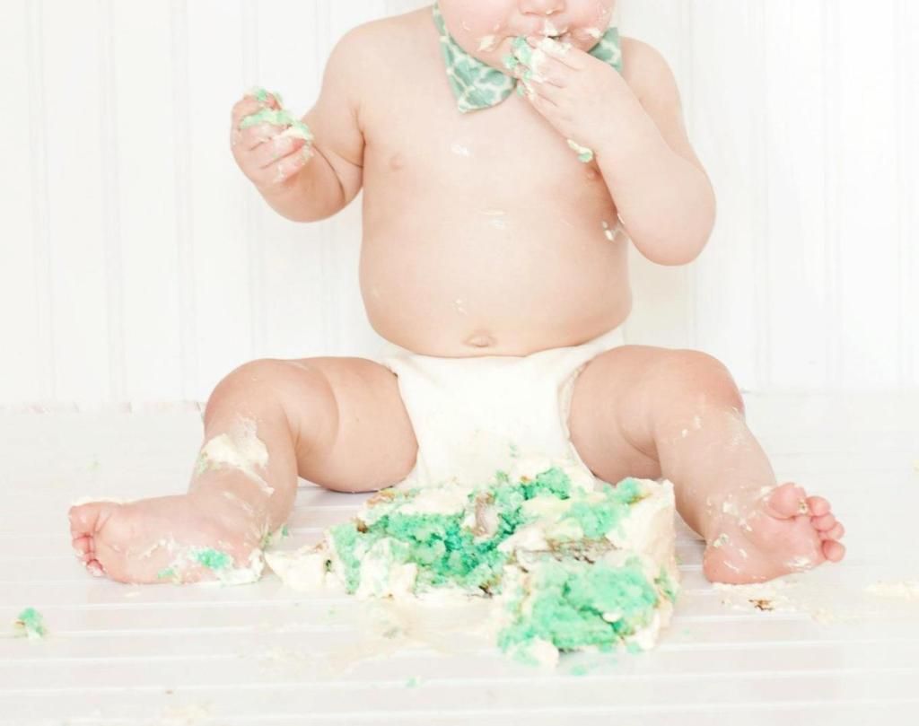 baby wearing cloth diaper eating blue free smash cake on floor