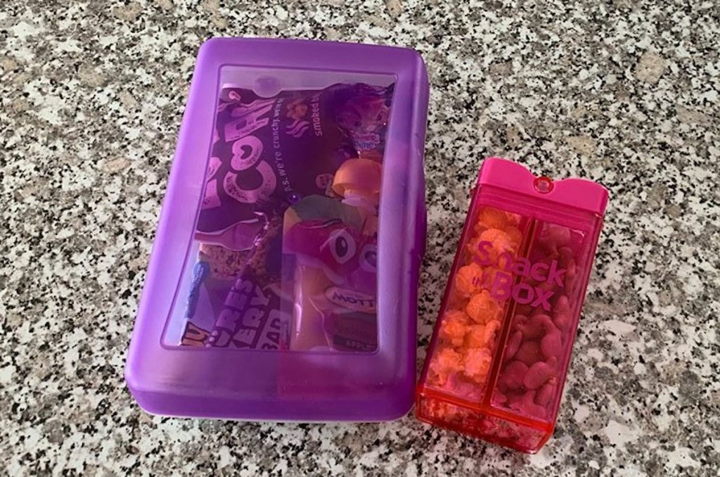 purple and pink snack boxes sitting on granite countertop