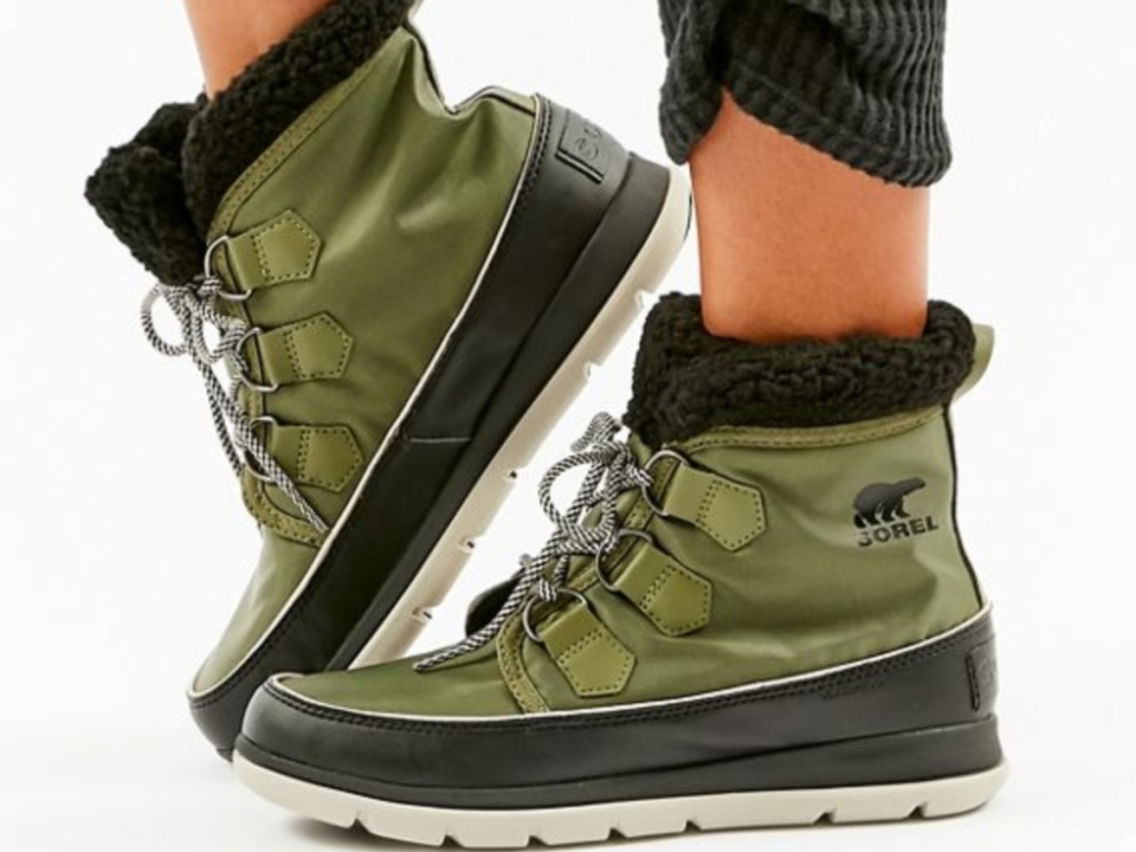 legs wearing green sorel boots