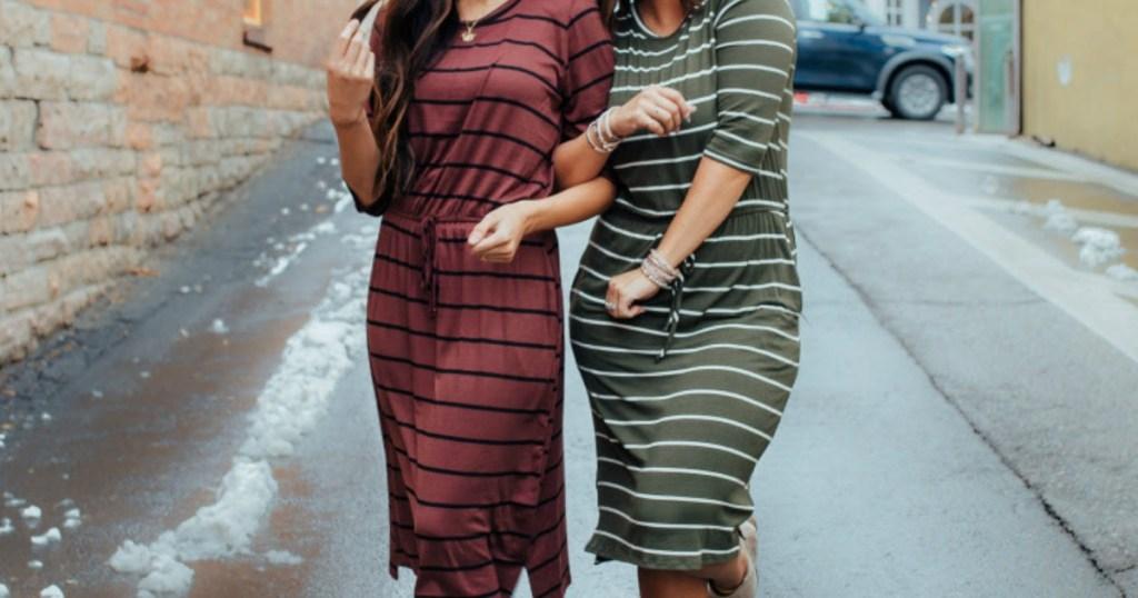 two women walking down the street in striped dresses