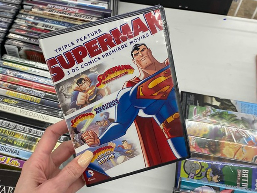 hand holding movie with Superman pictured on it
