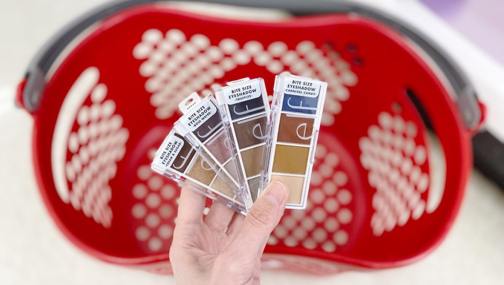 hand holding four different colors of shadow palettes with target basket in the background