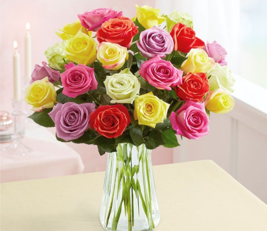 two dozen multi-colored roses in clear vase on table with candles in background