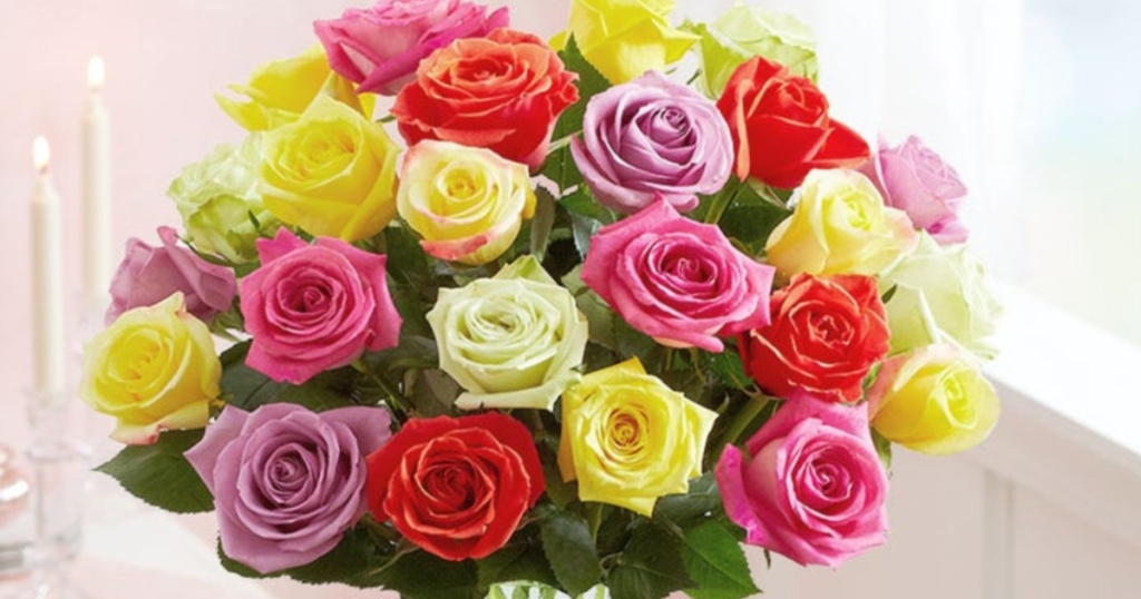 two dozen multi-colored roses with candles in background