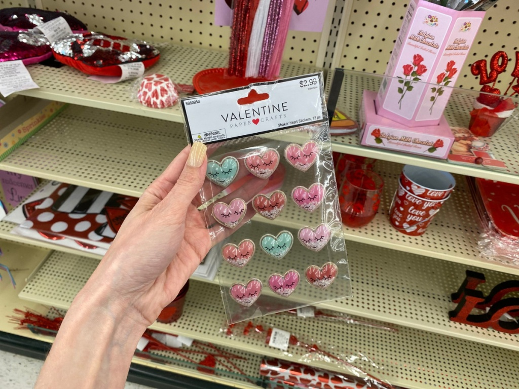hand holding valentines day stickers in store