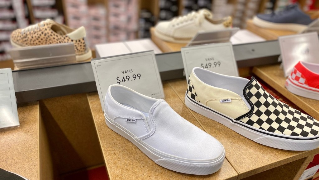 row of vans slip on shoes sitting on store shelf with price tags