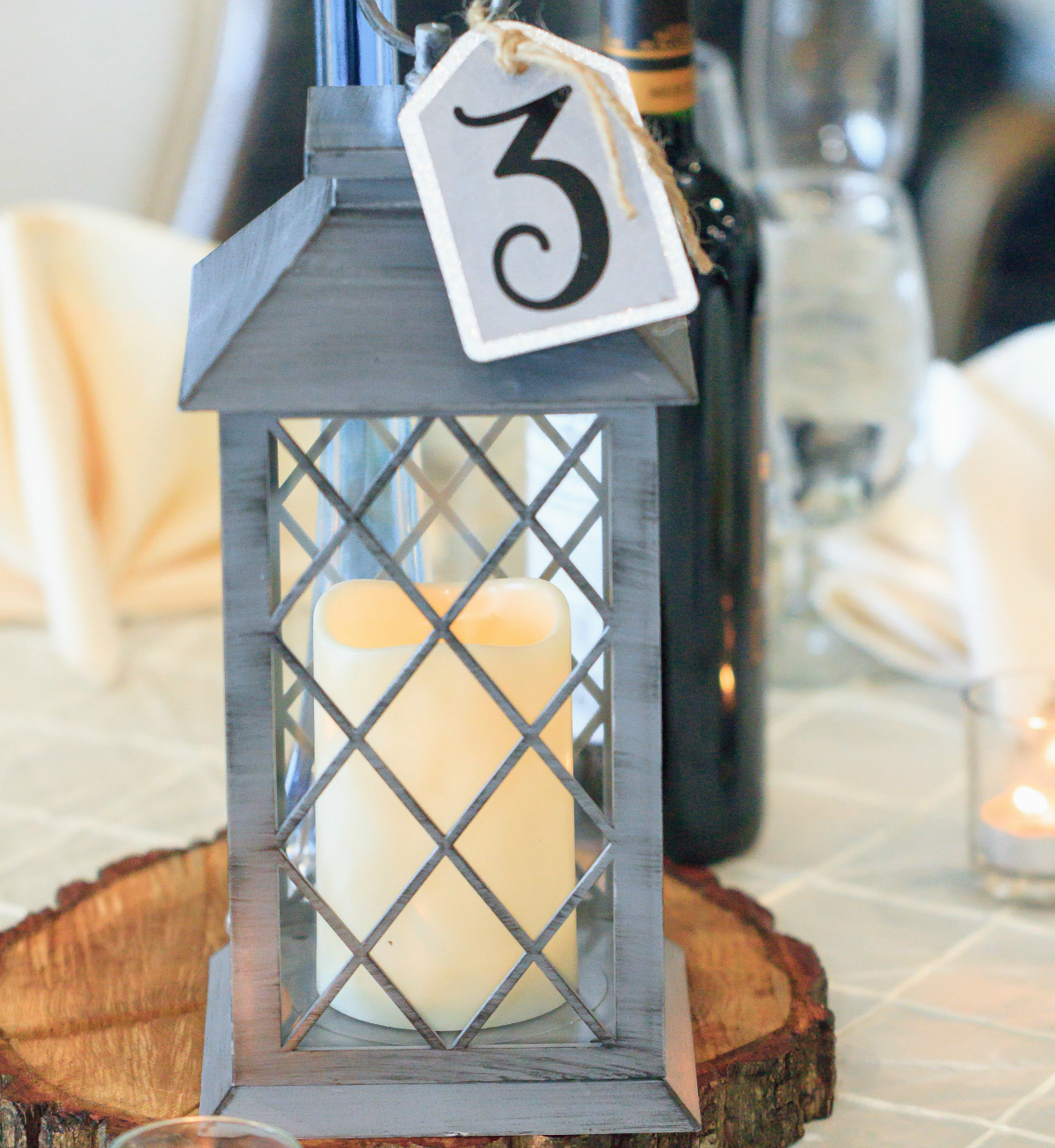 close up of metal lantern with candle inside and number 3 hanging from the top - dollar tree wedding