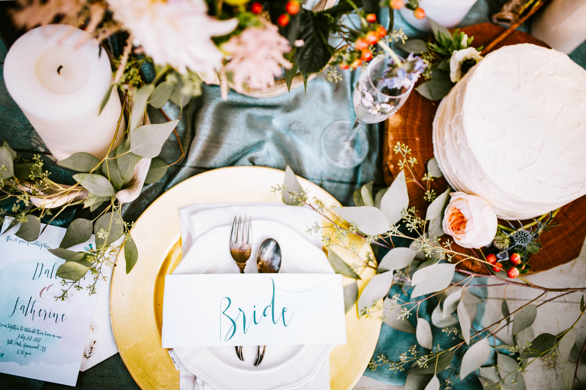 wedding table setting with flowers candles and cake