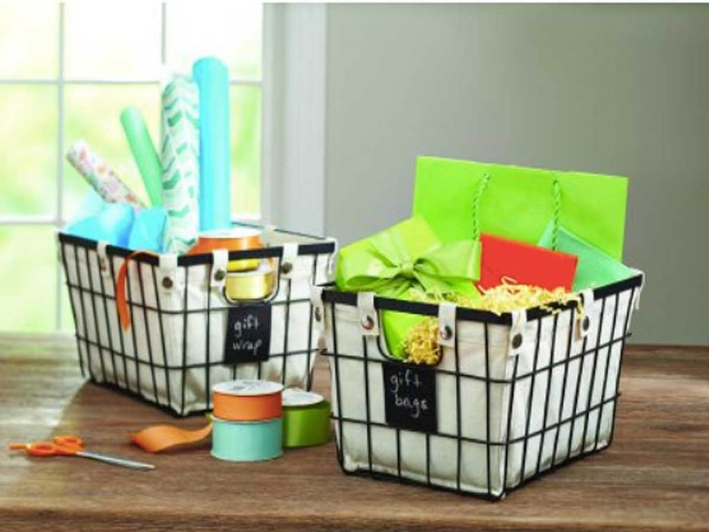 wire baskets with gift wrapping materials in them on a table
