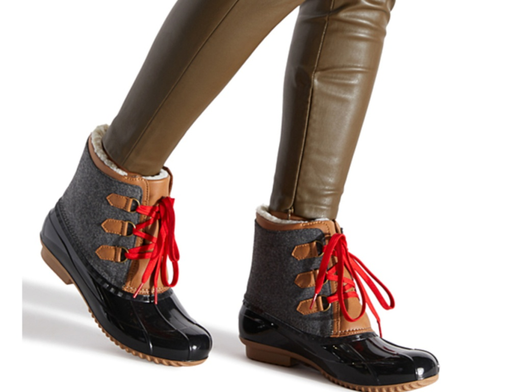 women's legs wearing blue, brown and black duck booties with red laces