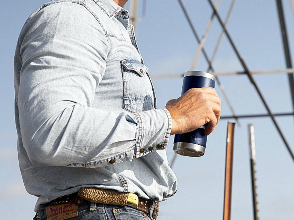 man in denim shirt holding drinking flask outside