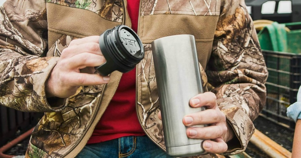 man with open lid to drinking flask in jacket outside