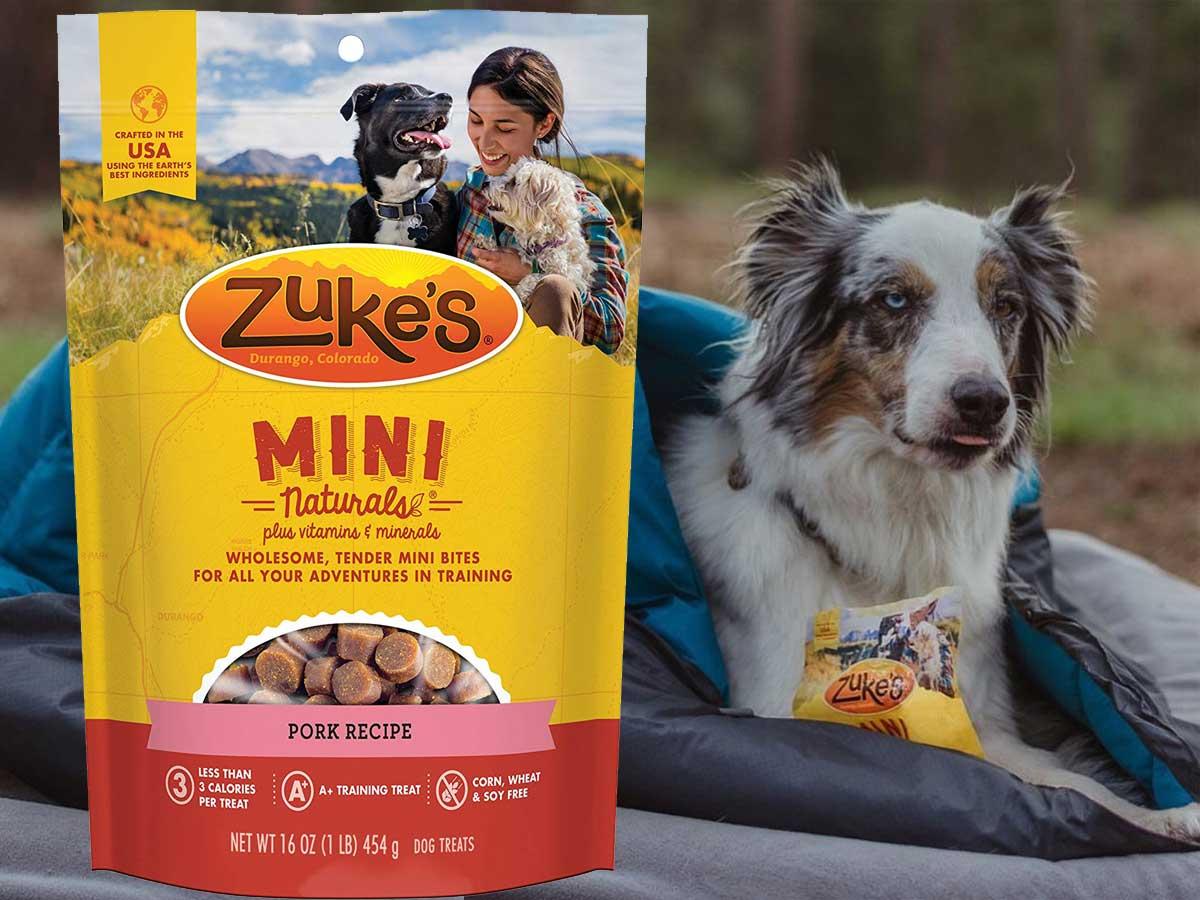 zuke's mini naturals dog treats with a dog laying by it