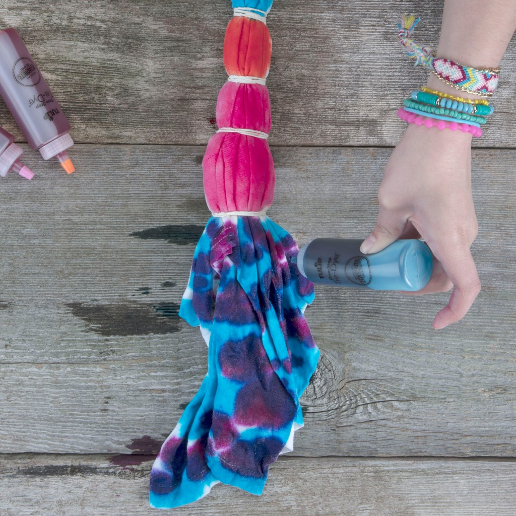 girls hand holding plastic squeeze bottle putting dye onto banded t-shirt for tie dye shirt project