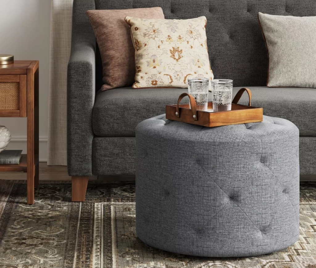 tufted ottoman with tray and glasses on top in living room in front of upholstered couch with three decorative throw pillows on it