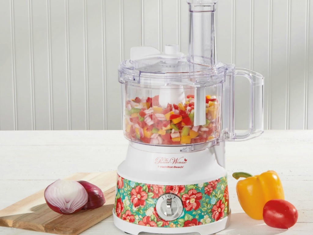 food processor on counter by onions and peppers