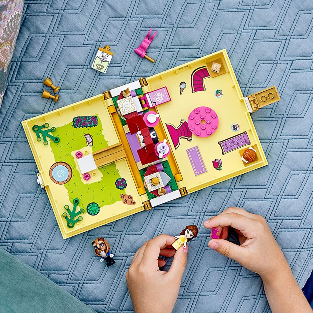 little girl playing with beauty and the beast storybook lego