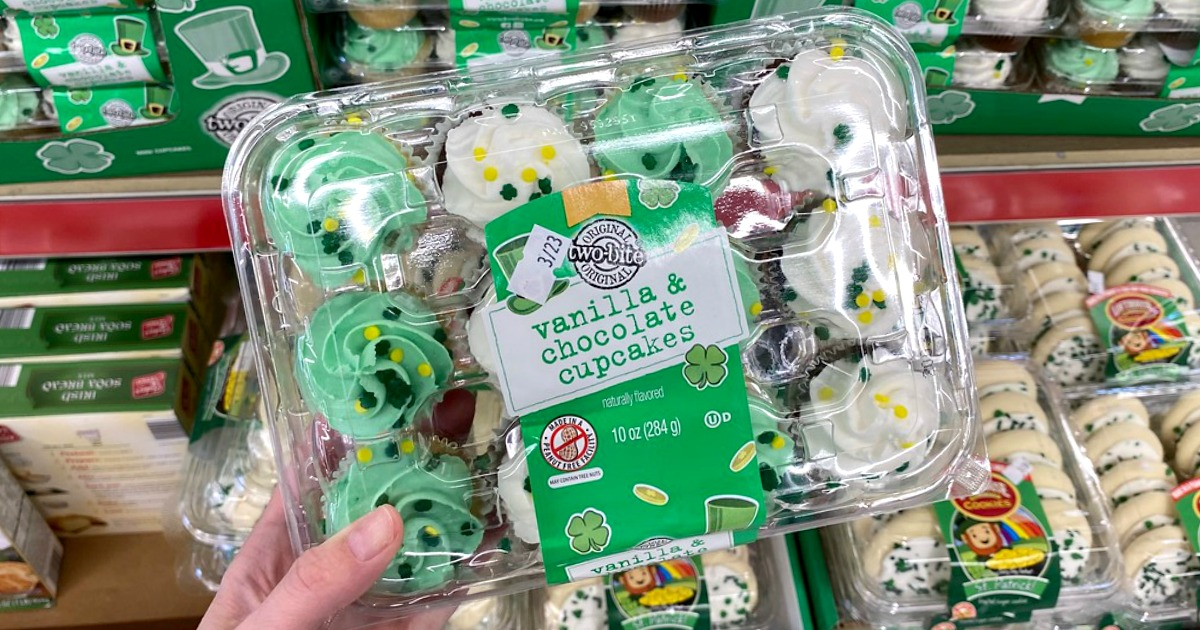 Woman holding up a plastic container of St. Patrick's Day themed cupcakes in-store