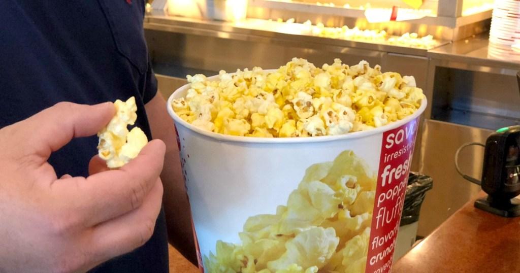 Hand grabbing popcorn from movie theater popcorn bucket