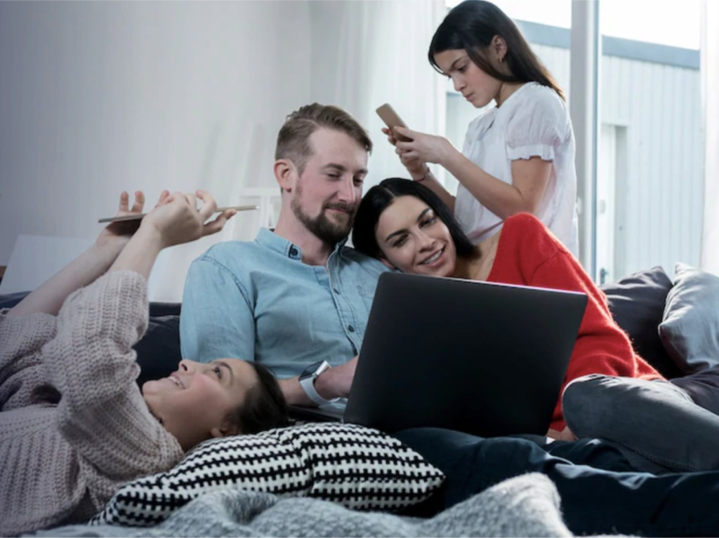 family together on couch using electronics