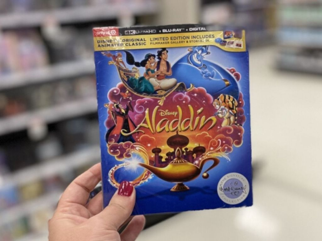 woman's hand holding Aladdin movie DVD at store