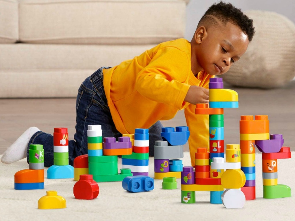 Young boy playing a set of multi-colored blocks