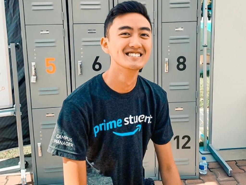 man sitting on a bench in front of lockers wearing prime student tee