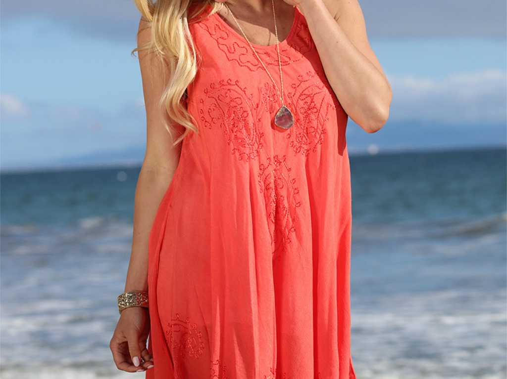 Woman in coral dress on the beacj