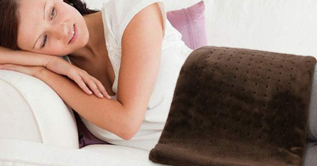 Woman laying on couch with Arealer heating pad