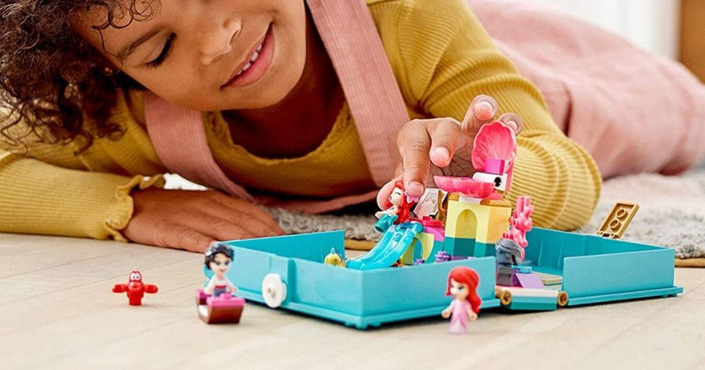 Little girl playing with lego storybook play set featuring the little mermaid