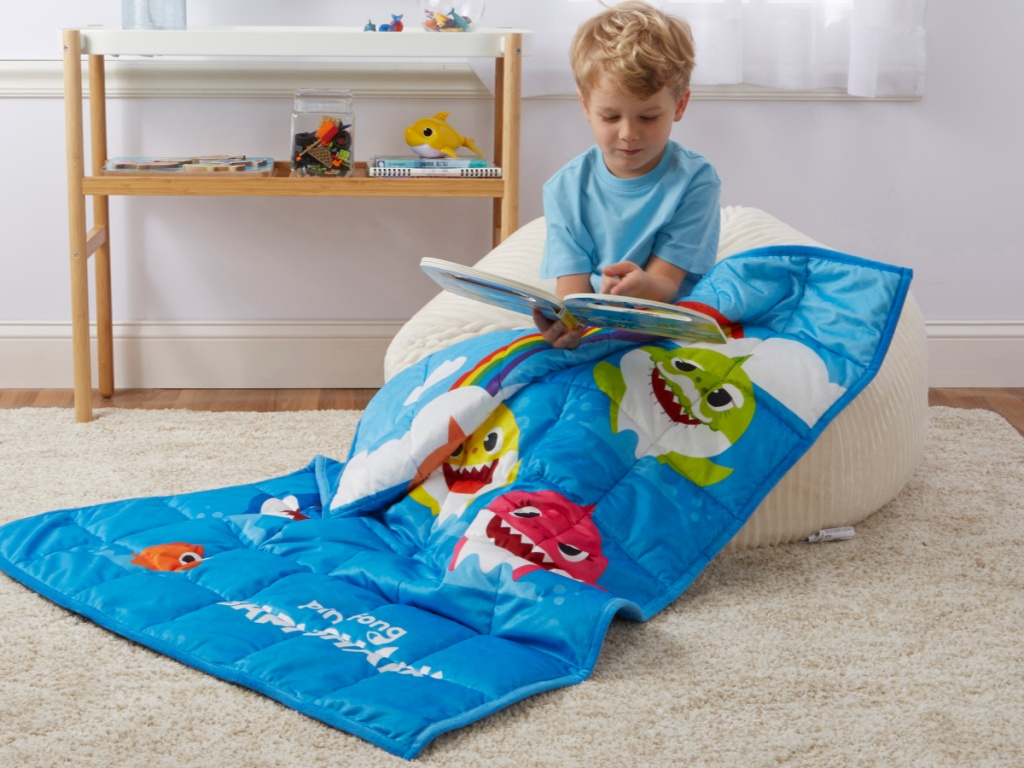 Little boy reading a book sitting under baby shark weighted blanket