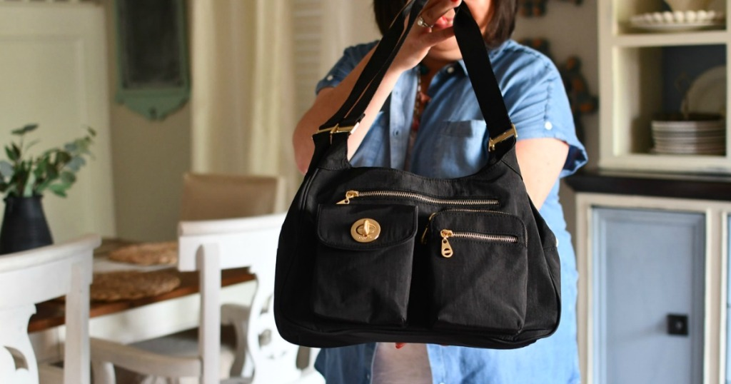 woman holding a large black purse with multiple pockets