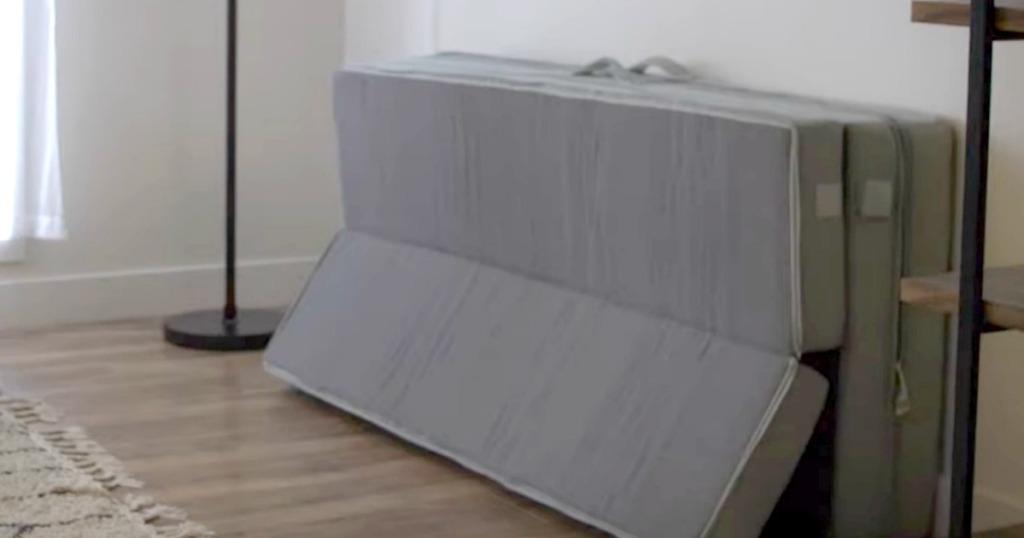 mattress topper laying on wall in livingroom