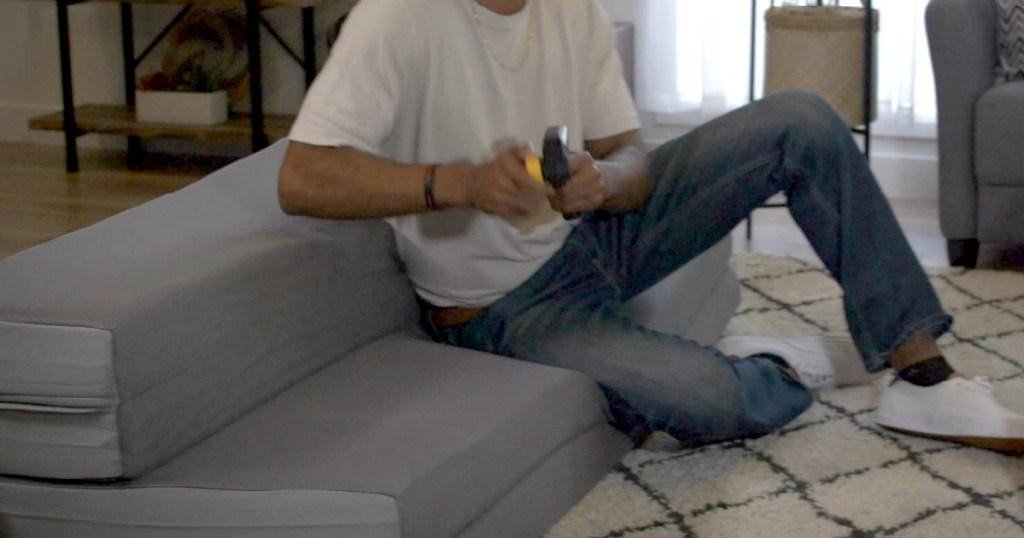 man sitting on mattress playing video game