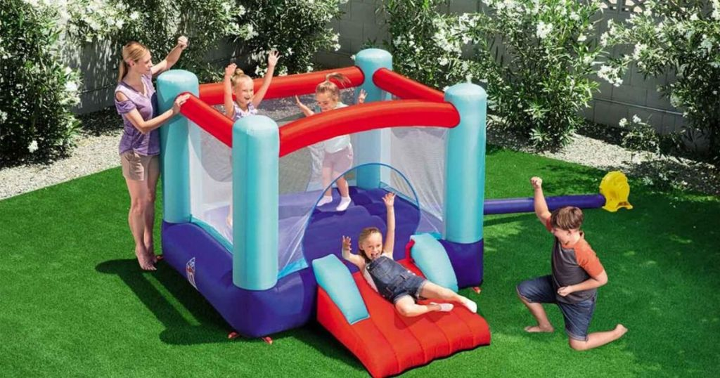 four kids and an adult playing on bounce house with slide outside on grass