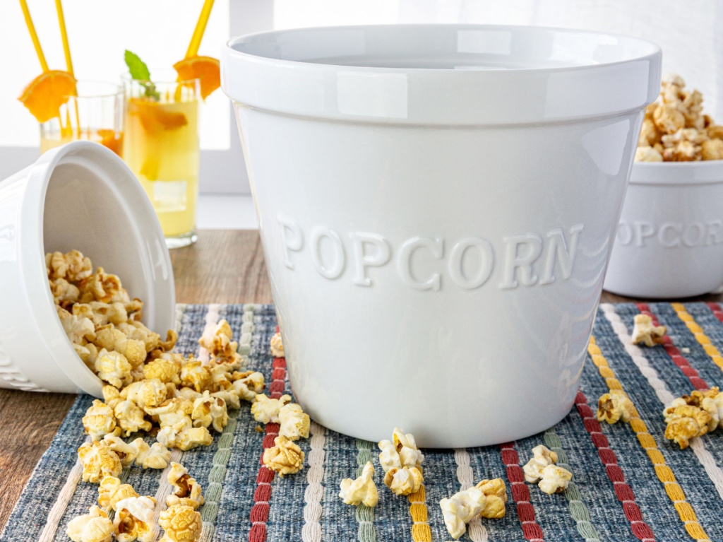 large white popcorn bowl on table with popcorn and drink